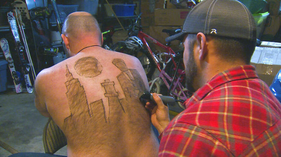 In this Dec. 29, 2015 photo provided by KTVB-TV, Tyler Harding, right, trims a design on Mike Wolfe out of his back hair in Nampa, Idaho. Wolfe and Harding meet up several times throughout the year to design a new creation on Wolfe's back. The designs have since been compiled for a calendar. (Mike di Donato/KTVB via AP) Photo: Mike Di Donato