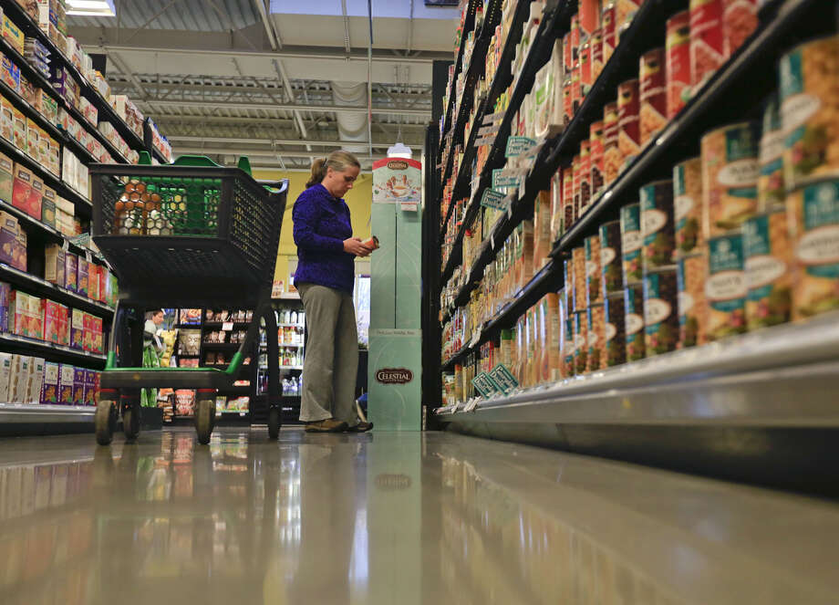 In this Tuesday, Dec. 15, 2015, photo, a shopper reads a food label at Honest Weight Food Co-Op in Albany, N.Y. Food cooperative programs that allow members to scoop rice, sort organic vegetables and ring up sales in return for grocery discounts are fading fast. (AP Photo/Mike Groll) Photo: Mike Groll