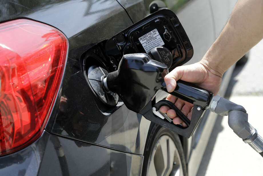 FILE - In this May 8, 2015 file photo, gas station attendant Carlos Macar pumps gas in Andover, Mass. Gasoline is close to breaking below a key psychological barrier as drivers enjoy some of the cheapest pump prices since the recession. The nationwide average price of a gallon of regular Saturday, Dec. 12, 2015 was $2.02, down 58 cents from this time last year, according to auto club AAA. Experts say it could drop below $2 in the coming days. (AP Photo/Elise Amendola, File) Photo: Elise Amendola