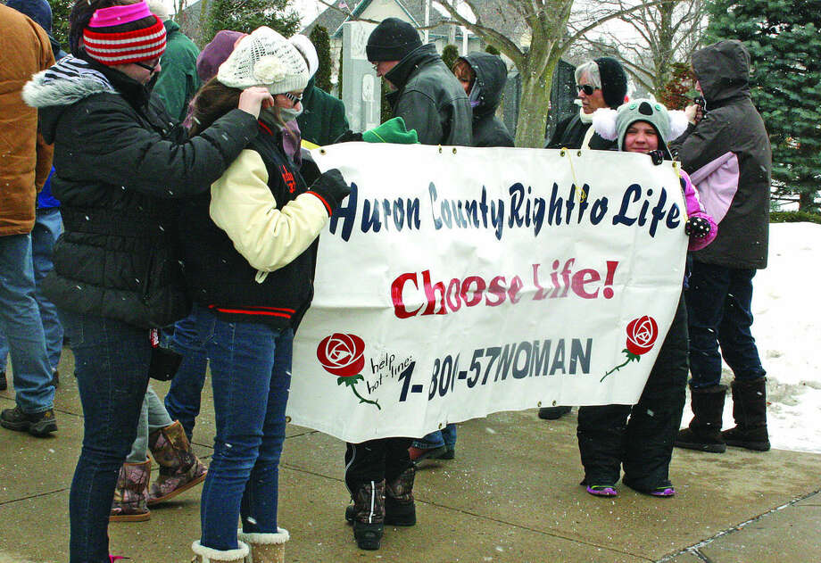 Pro-Right to Life youth hold a banner at the Huron County Right to Life Memorial Service on Sunday in Bad Axe.   Photo: Rich Harp/For The Tribune