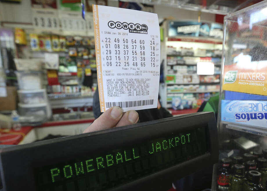 A convenience store employee holds a Powerball lottery ticket in Richmond, Va., Tuesday, Jan. 5, 2016. Multi-State Lottery Association officials say the Powerball jackpot is up to $450 million for Wednesday night's drawing. It's the largest lottery jackpot in nearly a year and the sixth-largest ever in North America. (AP Photo/Steve Helber) Photo: Steve Helber