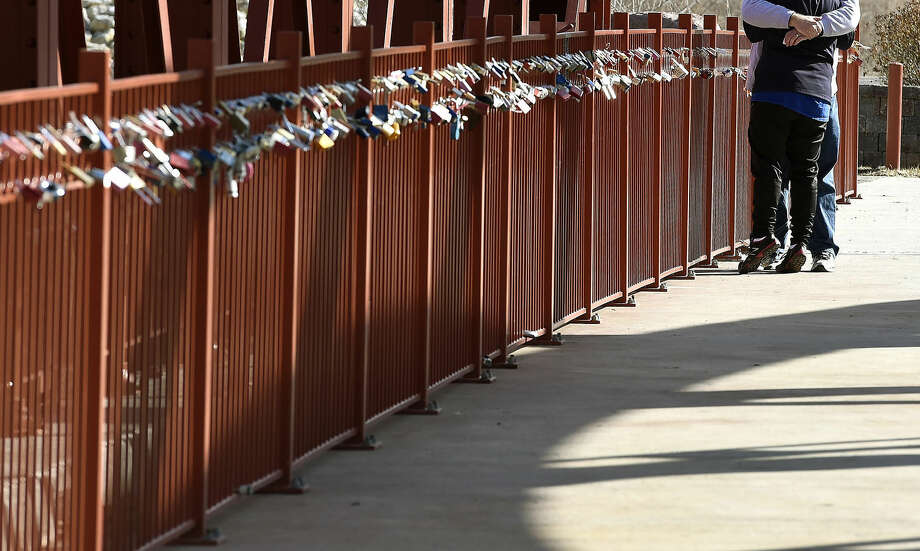 """FILE - In this Feb. 14, 2015 file photo, a couple hug after leaving a lock during """"Locking Your Love"""" to the Old Red Bridge Valentine's Day event at Minor Park in Kansas City, Mo. The bridge is located between Holmes and Blue River Roads and has become a popular place for couples to leave locks with messages on them. Most Americans think making a clean break with an ex helps speed the healing process after a breakup, according to a new Associated Press-WE tv poll. But not all of them are listening to their own advice. (John Sleezer/The Kansas City Star via AP, File ) Photo: John Sleezer"""