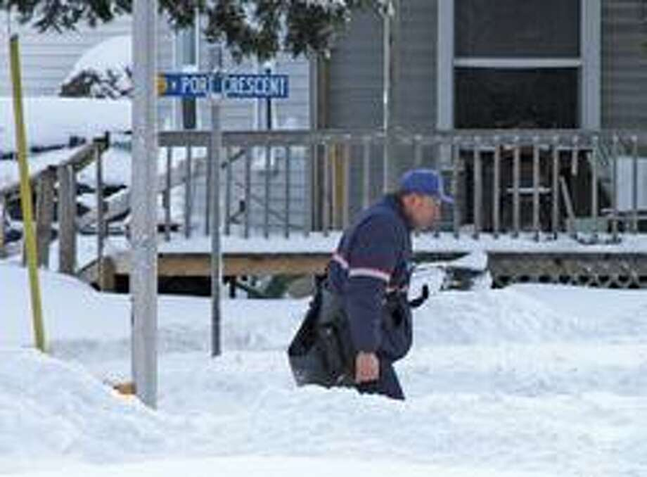 While some businesses in the area were closed, U.S. Postal Worker Alan White braves the wintery conditions to deliver the mail.