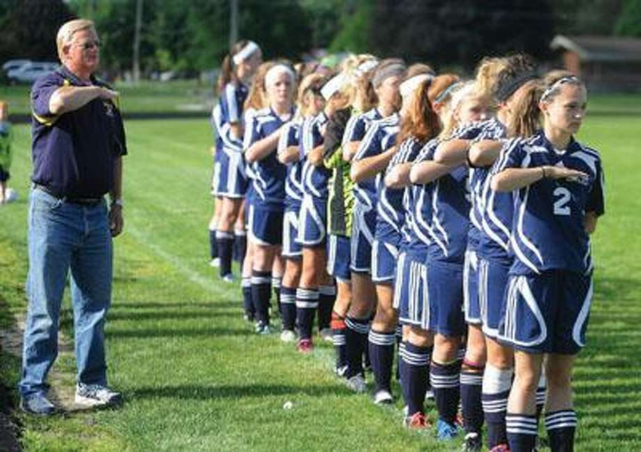 Bad Axe soccer coach Dave DeCourval and his girls team stand at attention for the national anthem during last year's regional semifinals at Saginaw. DeCourval passed away last week.
