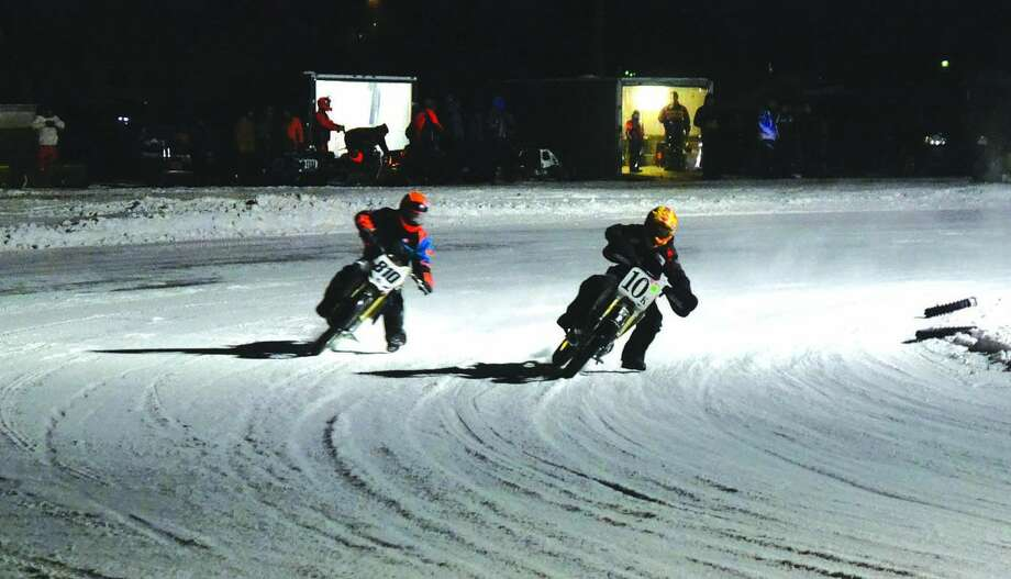 Two racers stir up snow-dust as they steer their dirtbikes around the brand new ice-track at MPX Racing in Sebewaing. Photo: Casey Johnson/For The Tribune