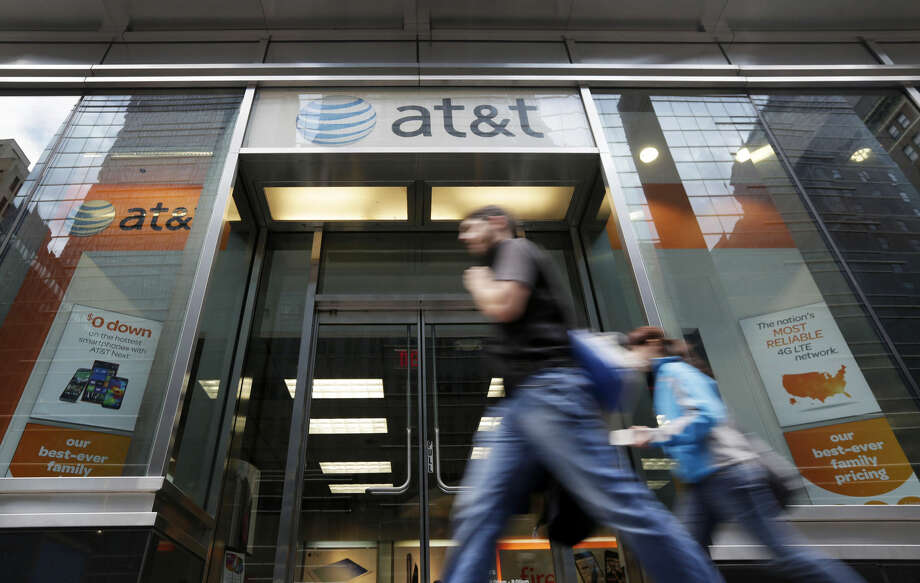 In this Tuesday, Oct. 21, 2014, photo, people pass an AT&T store on New York's Madison Avenue. AT&T is once again experimenting with offering unlimited data plans to smartphone customers while promoting its DirecTV service, signaling a potential reversal of industry trends toward data caps and charges for big video watchers. (AP Photo/Richard Drew) Photo: Richard Drew