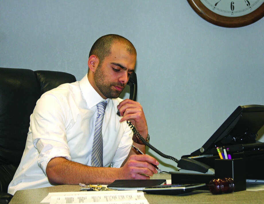 Village President Alex Khoury, 21, taking a phone call at the village hall on Friday, is believed to be the youngest current head of a municipal government in Michigan. Photo: Dave Shane/Huron Daily Tribune