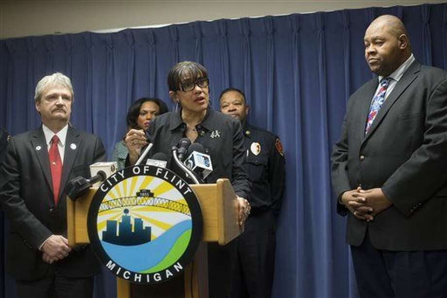 Flint Mayor Karen Weaver, center, speaks during a press conference Tuesday, Jan. 5, 2016, at City Hall, after Michigan Gov. Rick Snyder declared a state of emergency in the city over problems with lead in the city's drinking water. The city switched from Detroit's water system to Flint River water in a cost-cutting move in 2014, while under state financial management. Residents complained about the water's taste, smell and appearance, and children were found to have elevated levels of lead due to the water supply. (Conor Ralph/The Flint Journal-MLive.com via AP)