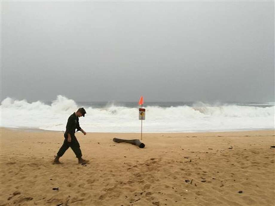 A U.S. Marine walks on the beach at Waimea Bay near Haleiwa, Hawaii, where two military helicopters crashed into the ocean about 2 miles offshore, Friday, Jan. 15, 2106. The helicopters carrying 12 crew members collided off the Hawaiian island of Oahu during a nighttime training mission, and rescuers are searching a debris field in choppy waters Friday, military officials said. (Mariana Keller via AP Photo)