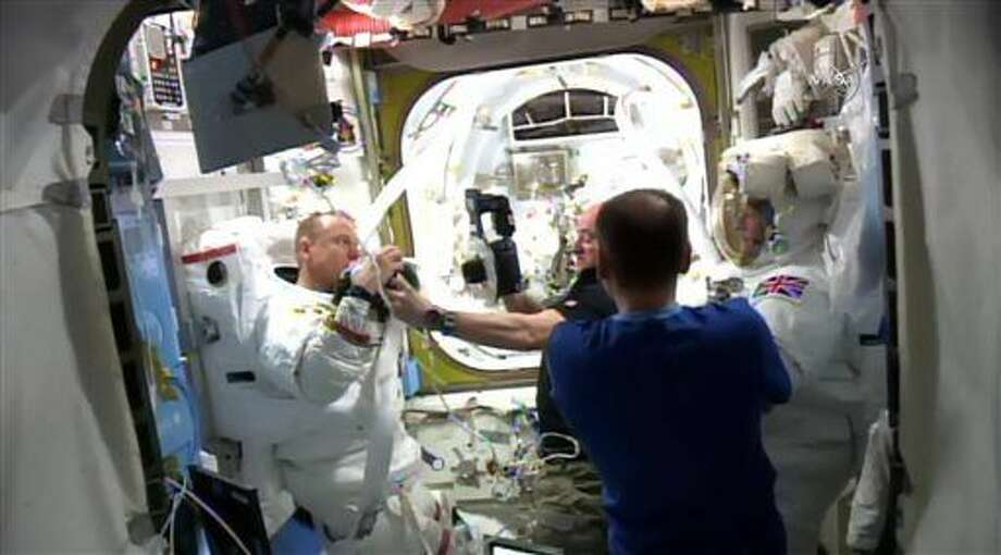 In this image made from video provided by NASA, astronaut Scott Kelly, center background, photographs parts of Timothy Kopra's spacesuit inside the International Space Station after a spacewalk with British spaceman Timothy Peake, right, was cut short after water leaked into Kopra's helmet. (NASA via AP)