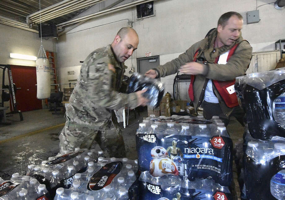 Michigan Nation Guard Sgt. Steve Kiger, left, of Harrison, Mich., stacks cases of drinking water with Red Cross volunteer Franklin Dickerson of Pleasant Ridge Wednesday Jan 13, 2016 in Flint, Mich. Members of the Michigan National Guard began arriving in Flint on Wednesday for briefings on the drinking water crisis, ahead of a larger contingent of Guardsmen who will help distribute bottled water, filters and other supplies to residents. (Dale G. Young/Detroit News via AP) Photo: Dale G. Young