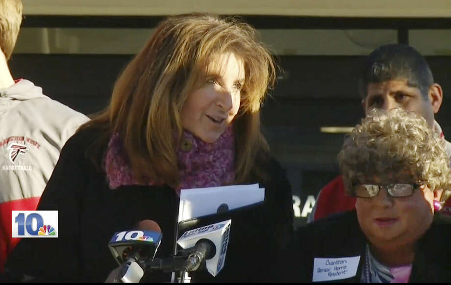 """In this Jan. 5, 2016 still image from WJAR-TV video, Sue Stenhouse, left, executive director of the Senior Enrichment Center, speaks alongside a man dressed as an elderly woman, right, during a news conference in Cranston, R.I., to promote a program for school children to help senior citizens shovel snow during the winter. The middle-aged male bus driver wore a wig, earrings, lipstick and a dress, and a tag that read, """"Cranston Senior Home Resident."""" Stenhouse resigned her position after the incident. (WJAR-TV via AP) MANDATORY CREDIT Photo: TEL"""