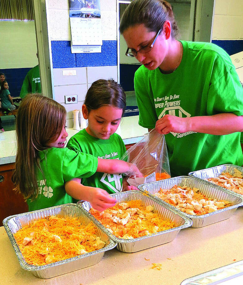 Christina Martens (far right) helps Addison Sattelberg (center) and Olivia Martens put on the top layer of cheese as 4-H children make food for families with cancer patients. Photo: Traci Weisenbach/For The Tribune