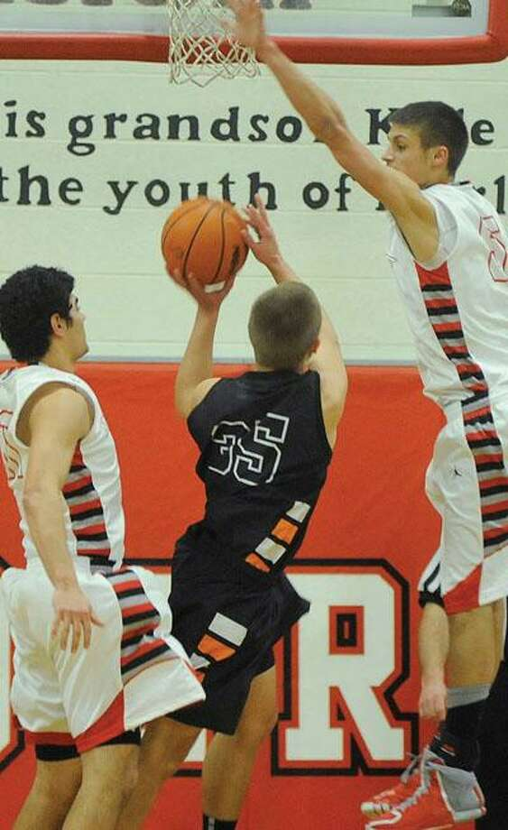 Harbor Beach's Colin Cook (35) puts up a shot between a pair of Marlette defenders, including Brad Schaub (right) during the first half of the Red Raiders' 63-60 win, Wednesday night in Marlette.