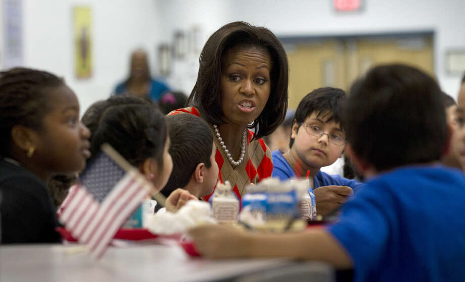 FILE - In this Jan. 25, 2012 file photo, First lady Michelle Obama has lunch with school children at Parklawn elementary school in Alexandria, Va. A bipartisan Senate bill released Monday would revise healthier meal standards put into place over the last few years to give schools more flexibility in what they serve the nation's schoolchildren, easing requirements on whole grains and delaying an upcoming deadline to cut sodium levels on the lunch line. (AP Photo/Pablo Martinez Monsivais) Photo: Pablo Martinez Monsivais