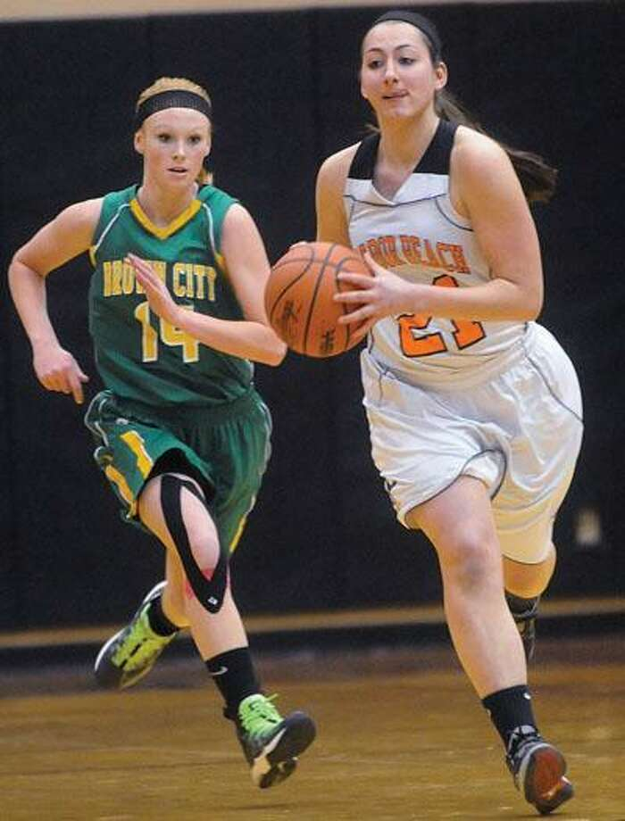 Harbor Beach's Jamie Weber (21) pushes the ball up the court, as Brown City's Abby Kaufman (14) trails during the first quarter of the Green Devils' 51-47 victory, Tuesday night in Harbor Beach.