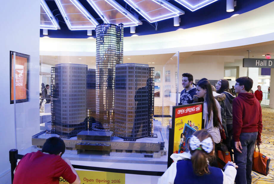 In this photo taken Monday, Jan. 18, 2016, attendees look at a replica of the Renaissance Center made out of Legos that is displayed at the Cobo Center during the North American International Auto Show in Detroit. (Romain Blanquart/Detroit Free Press via AP) Photo: Romain Blanquart