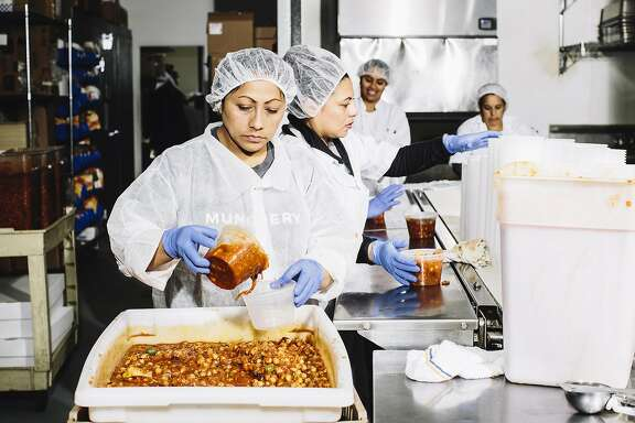Teresa Chable, a kitchen worker at Munchery, pours olive chickpea stew into a container at the company's kitchen in San Francisco, Calif. on Tuesday, April 19, 2016.