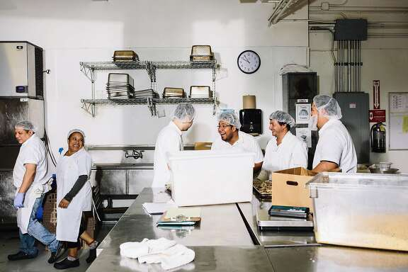 Kitchen workers share a joke inside the Munchery Kitchen in San Francisco, Calif. on Tuesday, April 19, 2016.