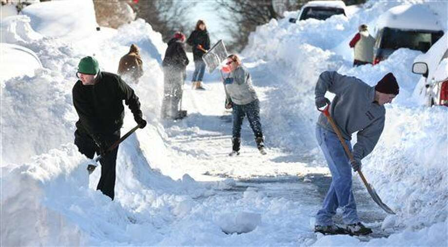Residents of W. Leicester St. in Winchester, Va. join forces to shovel out on Sunday, Jan. 24, 2016, after an historic snowstorm dumped more than 30 inches of snow on the city Friday night and Saturday. (Jeff Taylor/The Winchester Star via AP)