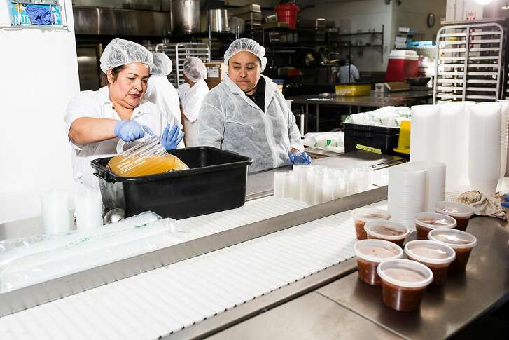 Reyna Sigoran, left, transfers sauce into a container at the plating station at the Munchery kitchen in San Francisco, Calif. on Tuesday, April 19, 2016.