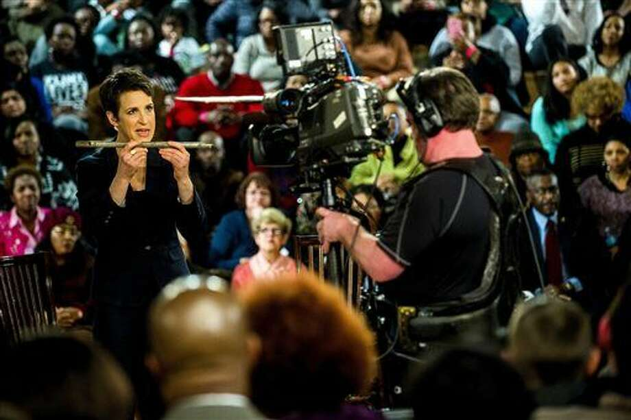 MSNBC's Rachel Maddow shows an example of a piece of galvanized pipe, which was cut out of the wall from Flint resident Harold Harrington's home during a television broadcast on Wednesday, Jan. 27, 2016 at Holmes STEM Academy in Flint, Mich. Flint residents coping with lead contamination will be cleared to drink unfiltered water again only when outside experts determine it is safe, Michigan Gov. Rick Snyder said Wednesday, acknowledging their mistrust of government officials while saying a full replacement of the city's pipes is not imminent. (Jake May/The Flint Journal-MLive.com via AP)