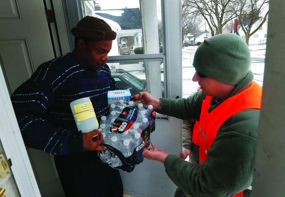 Louis Singleton receives water filters, bottled water and a test kit from Michigan National Guard Specialist Joe Weaver as clean water supplies are distributed to residents, Thursday, Jan. 21, 2016 in Flint, Mich. The National Guard, state employees, local authorities and volunteers have been distributing lead tests, filters and bottled water during the city's drinking water crisis. (AP Photo/Paul Sancya) Photo: Paul Sancya