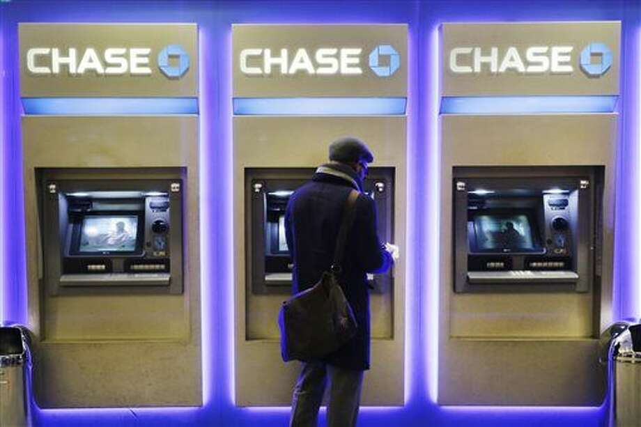 In this Wednesday, Jan. 14, 2015, file photo, a customer uses an ATM at a branch of Chase Bank, in New York. JPMorgan Chase will roll out later in 2016, new ATMs that will allow customers to access the machine or withdraw cash using their cellphone, the company said Monday, Jan. 25, 2016. The move will include new cash machines that don't require a card and upgrades to existing machines that will allow the customers to withdraw more money and in different denominations. (AP Photo/Mark Lennihan)