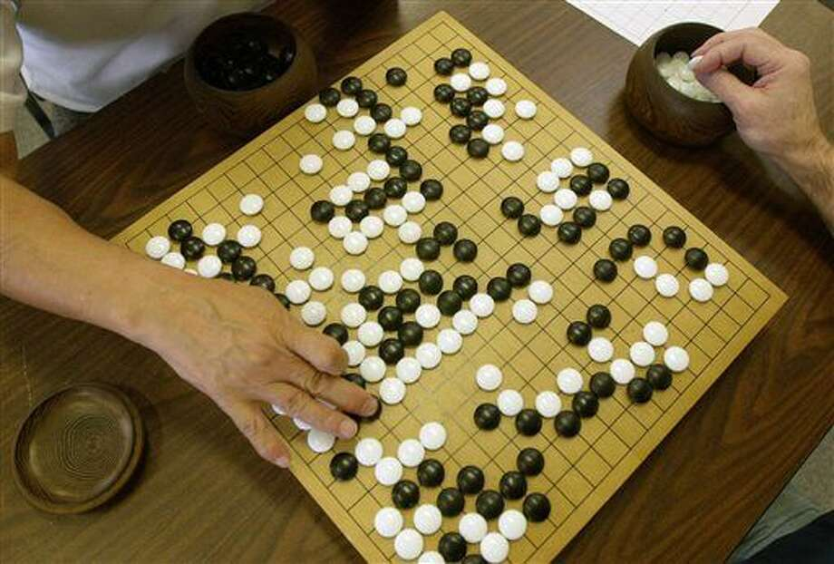 A player places a black stone while his opponent waits to place a white one as they play Go, a game of strategy, in the Seattle Go Center, Tuesday, April 30, 2002. The game, which originated in China more than 2,500 years ago, involves two players who take turns putting markers on a grid. The object is to surround more area on the board with the markers than one's opponent, as well as capturing the opponent's pieces by surrounding them. A paper released Wednesday, Jan. 27, 2016 describes how a computer program has beaten a human master at the complex board game, marking significant advance for development of artificial intelligence. (AP Photo/Cheryl Hatch)