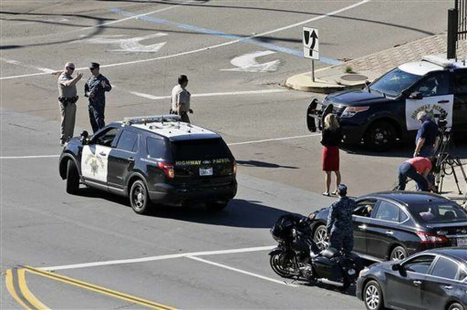 California Highway Patrol and military officers talk outside of the Naval Medical Center San Diego, Tuesday, Jan. 26, 2016, in San Diego. The Navy said authorities responded to a report of gunshots at a building on the campus. (AP Photo/Gregory Bull)