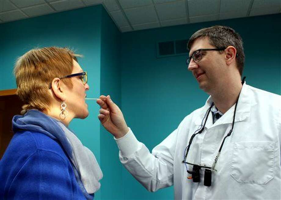 Dr. Jeffrey Huisman demonstrates how samples are taken for the bone marrow registry by swabbing the mouth of Linda Cooper, patient care coordinator, Monday, Jan. 25, 2016, at Huisman Family Dental in Holland Township, Mich. The practice will be encouraging patients to join the bone marrow registry through the Delete Blood Cancer DKMS campaign. (Amy Biolchini/Sentinel Staff)