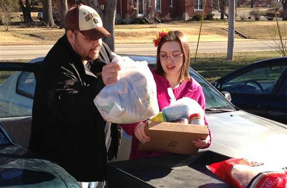 In this Jan. 28, 2016 photo, Joe Heflin, left, of Jefferson City, loads free groceries into the backseat of his car with the help from a volunteer at the Samaritan Center food pantry in Jefferson City, Mo. Heflin, 33, also receives federally funded food stamp benefits. He is among the more than 1 million people nationwide whose food stamps could end in three months if he doesn't meet work requirements or receive a disability exemption. (AP Photo/David A. Lieb)