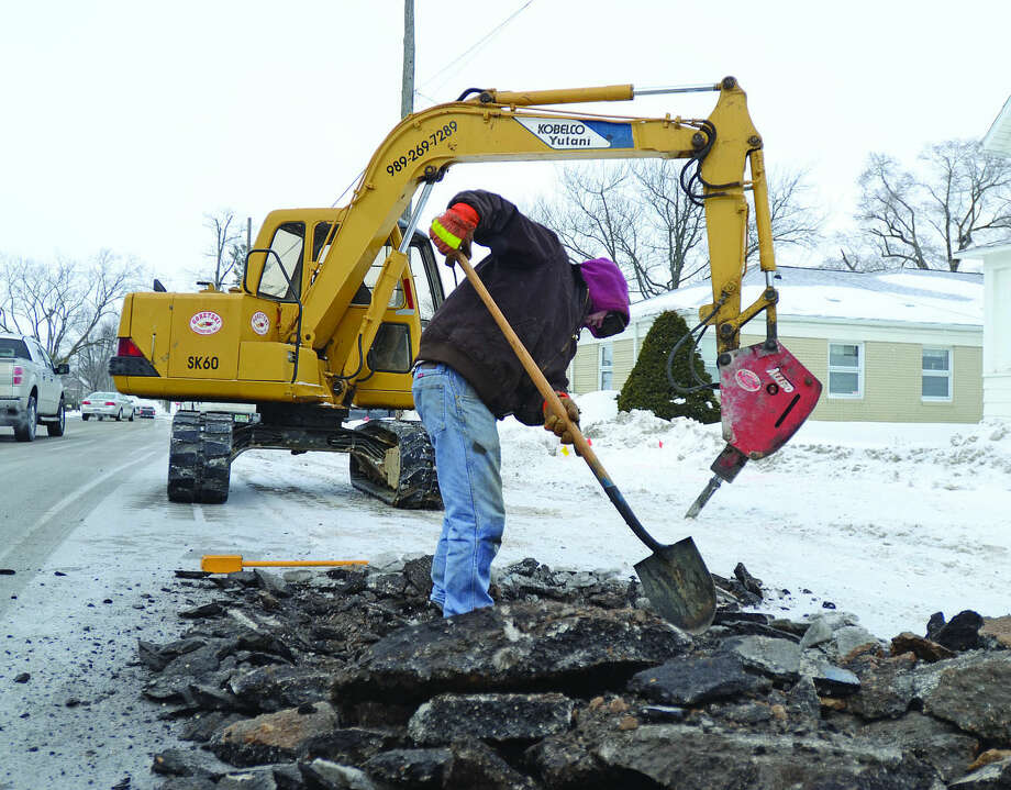 A worker addresses a frozen water line last week in the city of Bad Axe. Officials say municipal lines keep freezing and residents should continue to let water trickle for 24 hours a day. Photo: Chris Aldridge/Huron Daily Tribune