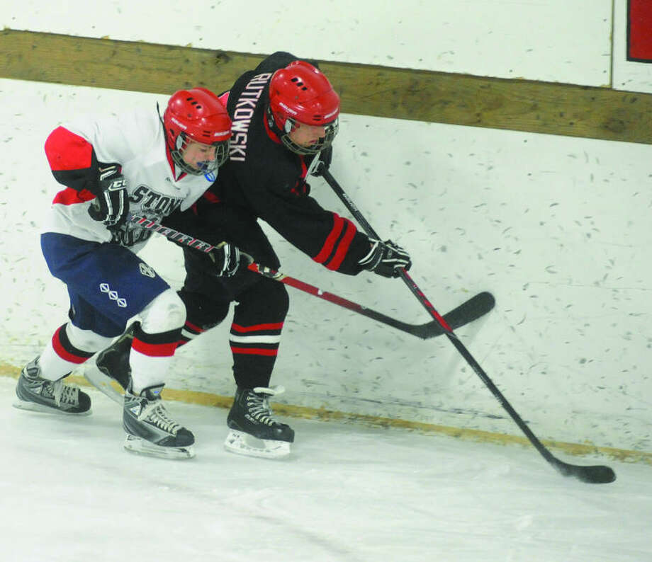 Stone Cold's Clare McManaman and Grindstone's Daniel Rutkowski contend for the puck along the boards during the first period.