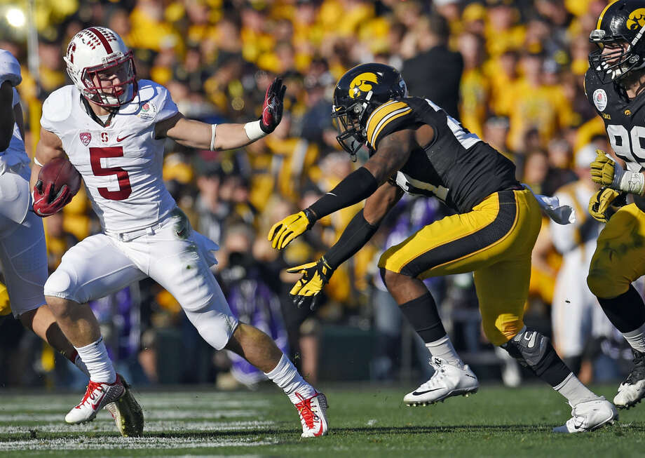 Stanford running back Christian McCaffrey, left, runs past Iowa defensive back Jordan Lomax during the first half of the Rose Bowl NCAA college football game, Friday, Jan. 1, 2016, in Pasadena, Calif. (AP Photo/Mark J. Terrill) Photo: Mark J. Terrill