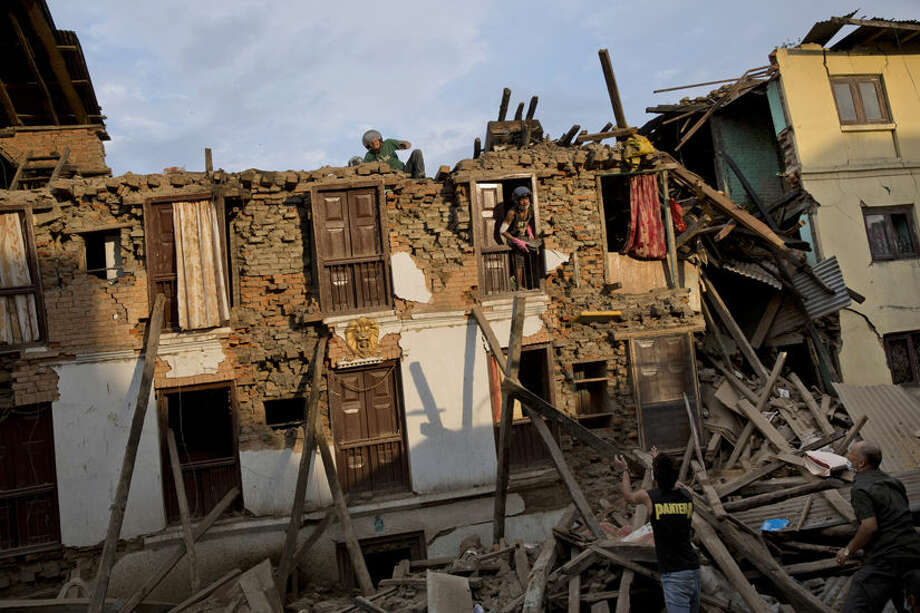 FILE - In this April 29, 2015 file photo Nepalese villagers salvage items from a house destroyed by Saturday's earthquake in Sakhu, on the outskirts of Kathmandu, Nepal. Last year saw the lowest financial costs from natural disasters worldwide since 2009 as the El Nino weather phenomenon reduced hurricane activity in the North Atlantic, a leading insurer said Monday, Jan. 4, 2016. (AP Photo/Bernat Amangue, file) Photo: Bernat Armangue