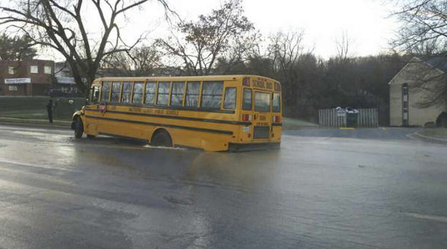 In this photo released by the Baltimore County Police, a school bus sits in a sinkhole, Wednesday, Jan. 6, 2015, in Cockeysville, Md. Baltimore County police say a school bus carrying high school students got stuck in a sinkhole after an overnight water main break, but the students got off safely. Police said in social media posts that the bus carrying Dulaney High School students got stuck Wednesday morning along Cranbrook Road in Cockeysville, near the water main break. (Baltimore County Police via AP) Photo: HOGP