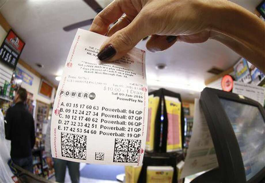 In this photo made with a fisheye lens a clerk hands a patron his $10 worth of chances for the upcoming Powerball drawing on Saturday, Jan. 9, 2016, in Cranberry Township, Pa. The Powerball jackpot has reached a record $900 million, with the drawing Saturday night. (AP Photo/Keith Srakocic) Photo: Keith Srakocic