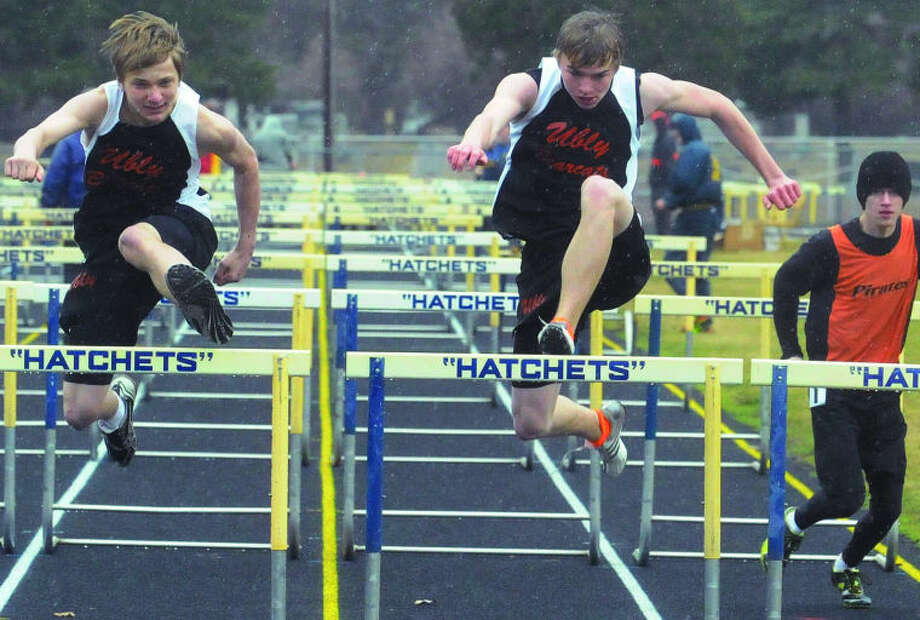 Ubly teammates Jonathan Wright (left) and Roger Franzel (right) clear the final set of hurdles in the 110 race, Thursday at a quad track & field meet in Bad Axe. The duo ended up tying for first. Also pictured is Harbor Beach's Eric VerEllen.