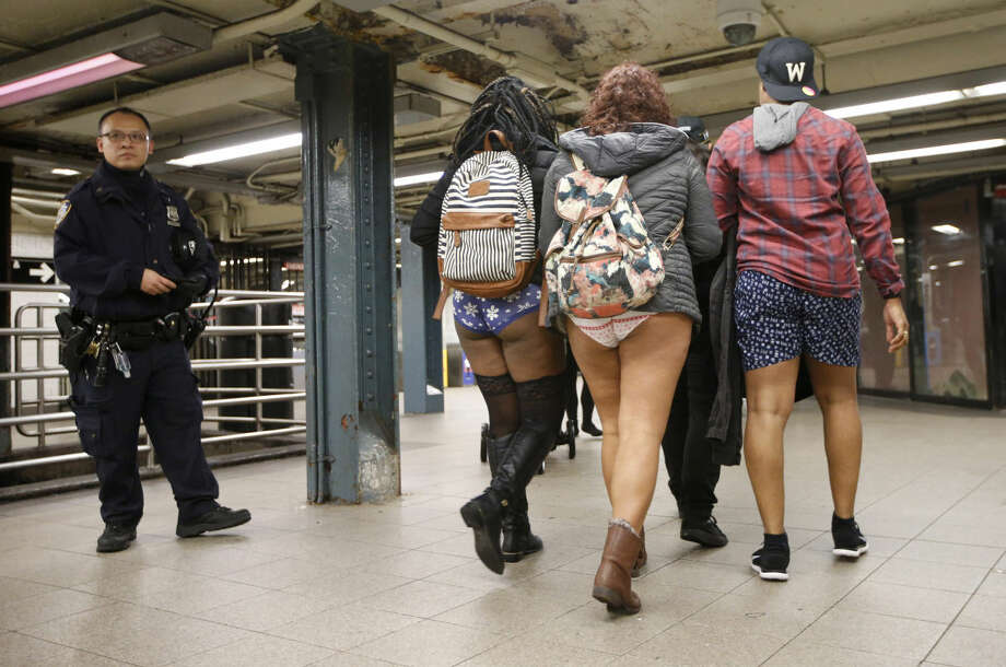 A police officer stands guard in a Manhattan subway station as three pantless people stroll by during the 15th annual No Pants Subway Ride, Sunday, Jan. 10, 2016, in New York. The group prank, meant to amuse, has been going on since 2002. (AP Photo/Kathy Willens) Photo: Kathy Willens