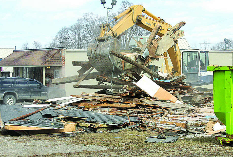 A Bad Axe home is removed Monday to allow for a fitness club's expansion.