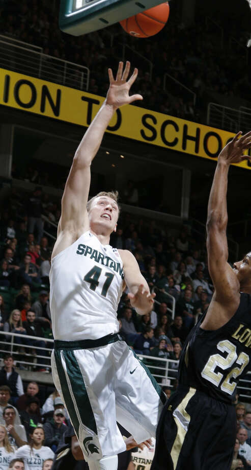 FILE - In this Nov. 20, 2015, file photo, Michigan State's Colby Wollenman, left, shoots against Arkansas-Pine Bluff's JoVaughn Love, right, during the first half of an NCAA college basketball game, in East Lansing, Mich. While the fourth-ranked Michigan State Spartans enjoyed a day off Monday, Jan. 11, 2016, center Colby Wollenman was interviewing for a spot in medical school.(AP Photo/Al Goldis, Fle) Photo: Al Goldis