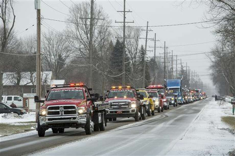 Tow trucks drive along West Water Street during a funeral procession for Jason Schultz in Port Huron Township, Mich., Wednesday, Jan. 20, 2016. Schultz, 28, the owner of Preferred Towing in Port Huron, was pulling a vehicle out of a ditch on Jan. 15, when he was struck and killed. (Jeffrey M. Smith/The Times Herald via AP)