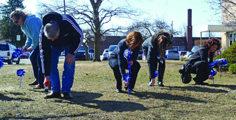 Huron County Commissioner Clark Elftman (second from left) drills holes in the ground while other volunteers plant pinwheels Wednesday on the front lawn of the county building. The pinwheels are a reminder of child abuse awareness and prevention. Photo: Chris Aldridge/Huron Daily Tribune