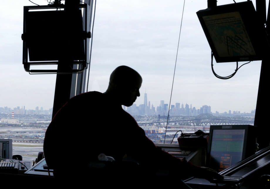 FILE - In this May 21, 2015 file photo, an air traffic controller works in the tower at Newark Liberty International Airport in Newark, N.J. A government watchdog says that despite a doubling of spending on air traffic control operations over two decades, productivity has declined and reform efforts have been ineffective. The report by the Department of Transportation's Inspector General may boost efforts by some lawmakers, airlines and others to remove air traffic operations from the Federal Aviation Administration's control and turn them over to a nonprofit corporation. ( AP Photo/Julio Cortez, File) Photo: Julio Cortez
