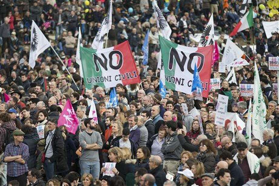 People hold flags reading in Italian ' No to civil unions ', as they gather at Rome's Circus Maximus, Saturday, Jan. 30, 2016. Thousands of people were gathering in Rome's Circus Maximus for a pro-family protest that opposes proposed legislation permitting civil unions for same-sex couples and legal recognition for their families. (AP Photo/Andrew Medichini)