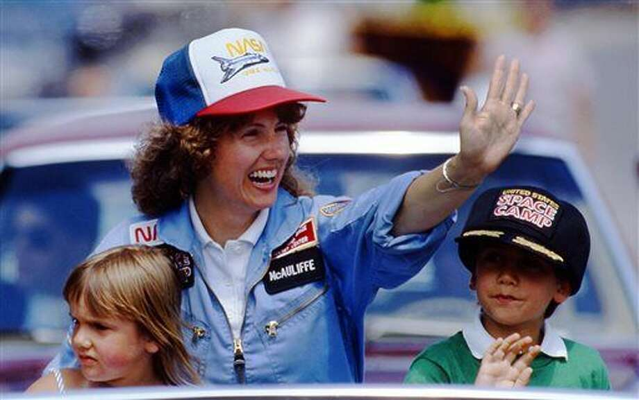 In this 1985 photo, high school teacher Christa McAuliffe rides with her children Caroline, left, and Scott during a parade down Main Street in Concord, N.H. McAuliffe was one of seven crew members killed in the Space Shuttle Challenger explosion on Jan. 28, 1986. (AP Photo/Jim Cole)