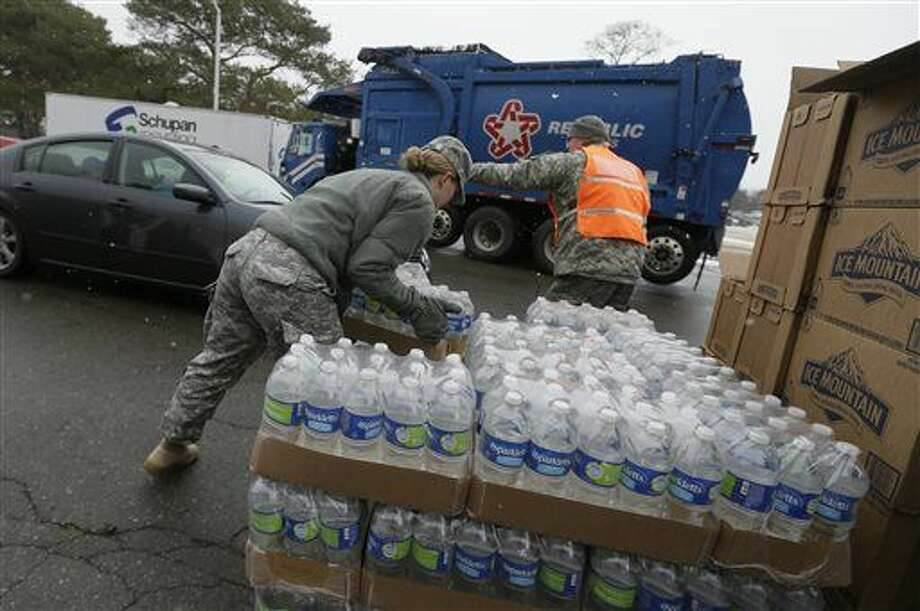 Members of the Michigan National Guard load bottled water at a fire station, Thursday, Jan. 28, 2016 in Flint, Mich. The Michigan Legislature voted Thursday to direct another $28 million to address Flint's water emergency, allocating money for bottled water, medical assessments and other costs in the city struggling with a lead-contaminated supply. (AP Photo/Carlos Osorio)