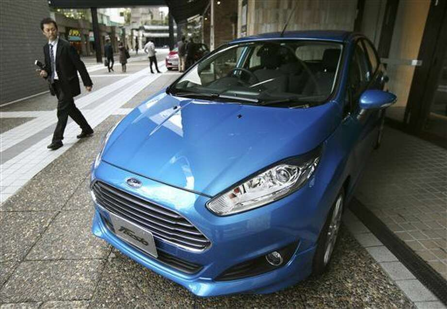 "In this Thursday, Jan. 9, 2014, file photo, a man looks at a Ford Fiesta compact car in Tokyo. Ford Motor Co. said Monday, Jan. 25, 2016, that it's pulling out of Japan and Indonesia before the end of the year because there is no path to grow sales or make sustained profits. The automaker says ""market dynamics"" prevent it from competing effectively in both of the countries, so it will cease operations and concentrate resources elsewhere. (AP Photo/Koji Sasahara)"