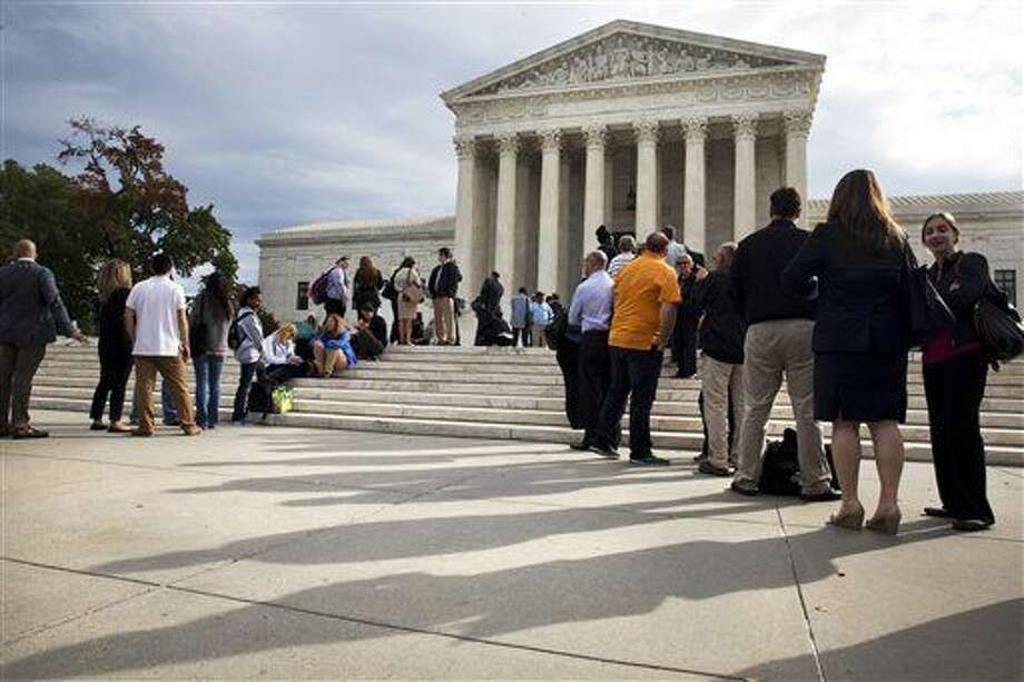 In this Oct. 13, 2015 file photo, people line up outside of the Supreme Court in Washington, Tuesday, Oct. 13, 2015, as the justices began to discuss sentences for young prison 'lifers.' A decision in Montgomery v. Louisiana. The Supreme Court ruled Monday, Jan. 25, 2016, that people serving life terms for murders they committed as teenagers must have a chance to seek their freedom. The court ruled in the case of Henry Montgomery, who has been in prison more than 50 years, since he killed a sheriff's deputy as a 17-year-old in Baton Rouge, Louisiana, in 1963. (AP Photo/Jacquelyn Martin)
